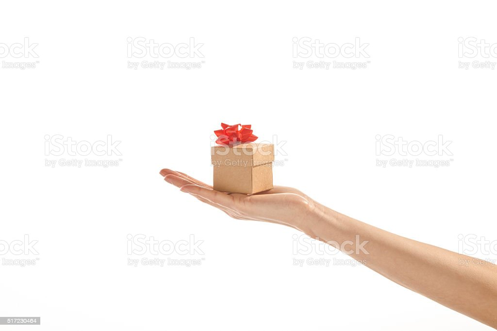 Hand holding tiny gift box at fingertips stock photo