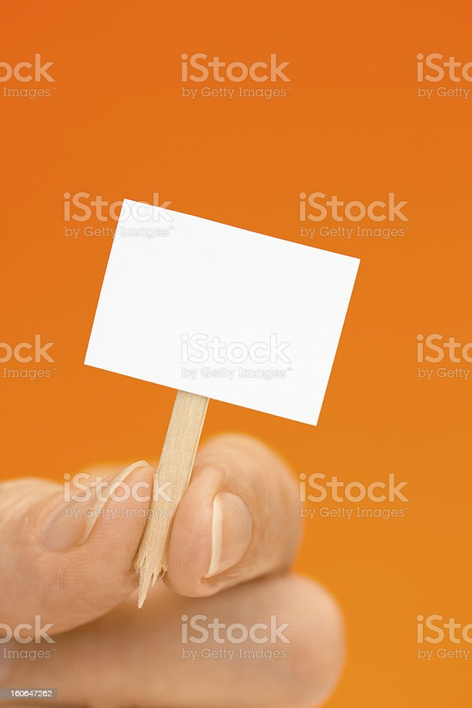 Hand Holding Tiny Sign on Orange with Copy Space royalty-free stock photo