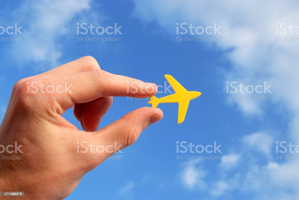 Hand holding tiny yellow airplane against blue sky royalty-free stock photo