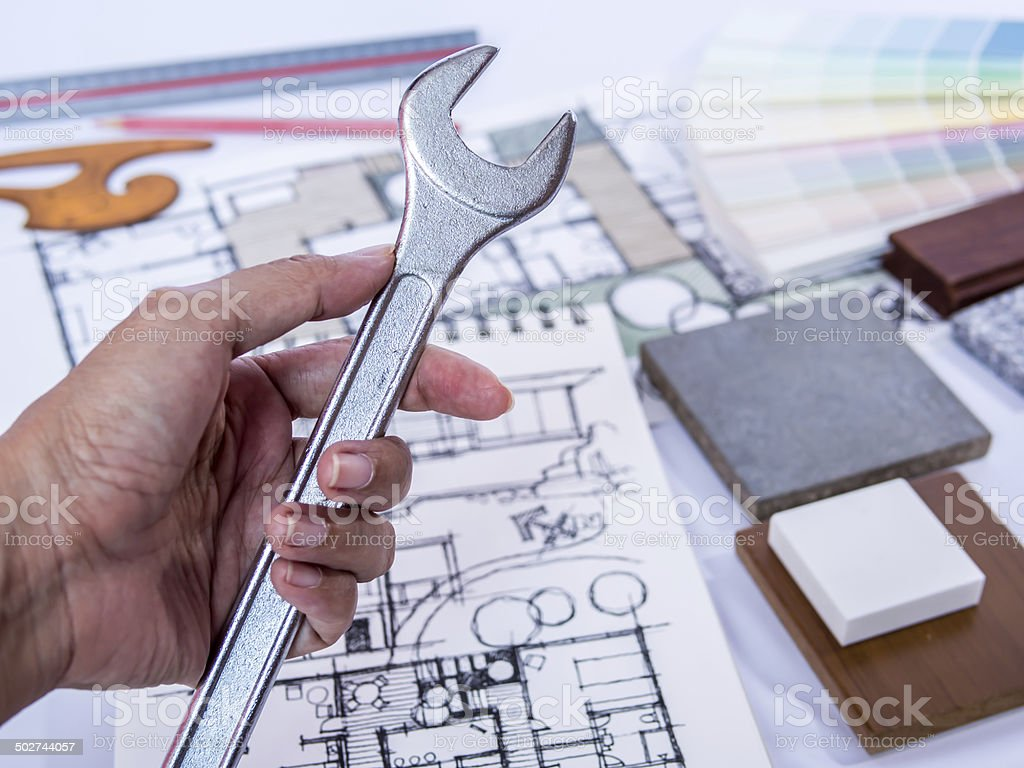 Hand holding tool, concept of  home renovation with architecture drawing stock photo