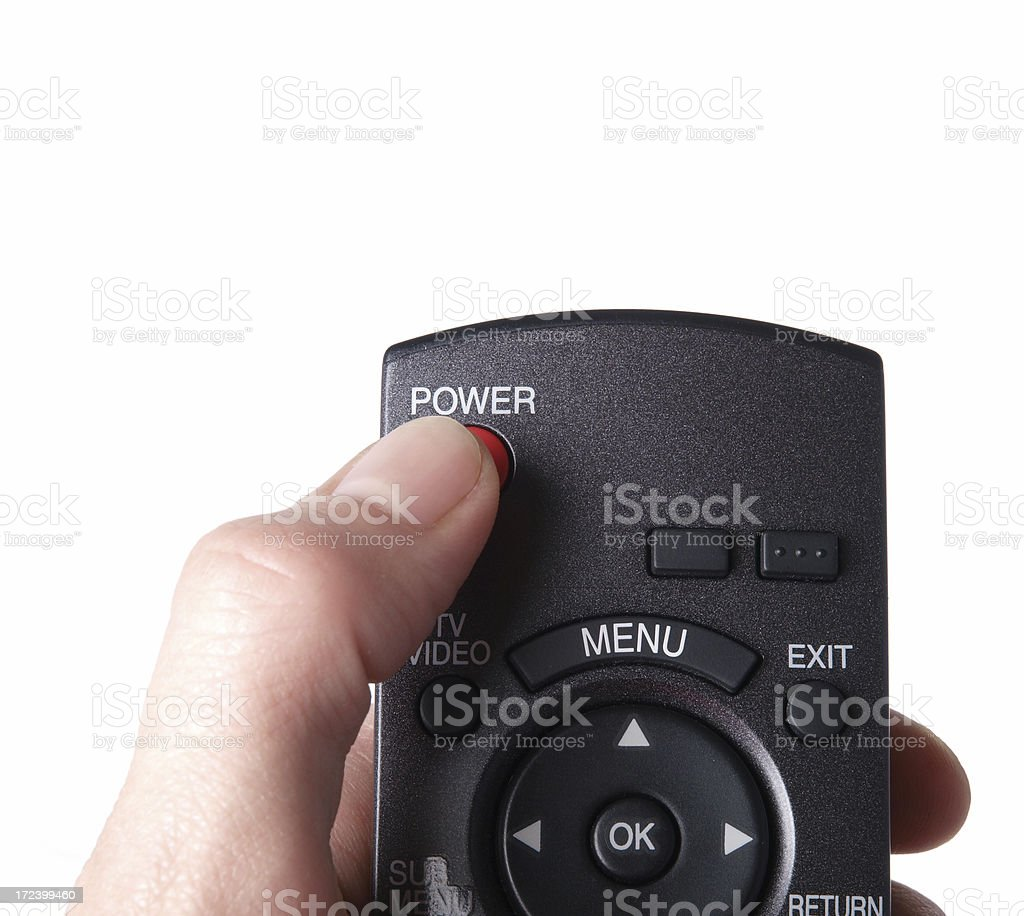 Hand holding TV remote, thumb on power button royalty-free stock photo