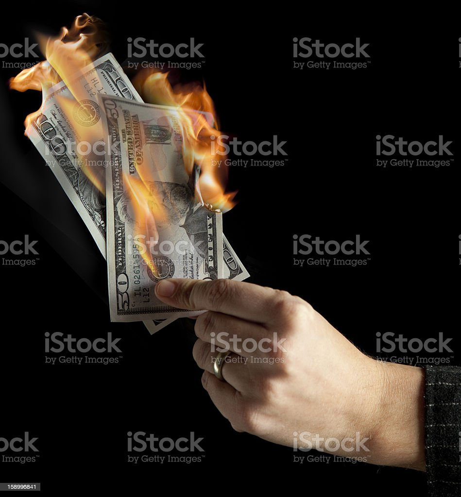 A hand holding two burning paper bills stock photo