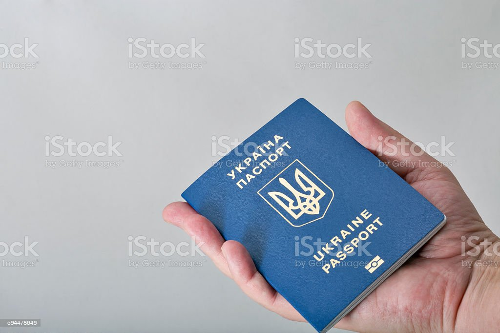 Hand holding Ukrainian biometric passport on white background stock photo