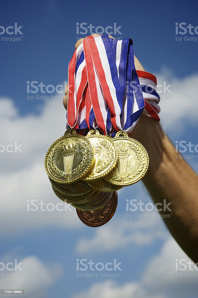 Hand Holding Up a Bunch of Gold Medals Blue Sky royalty-free stock photo