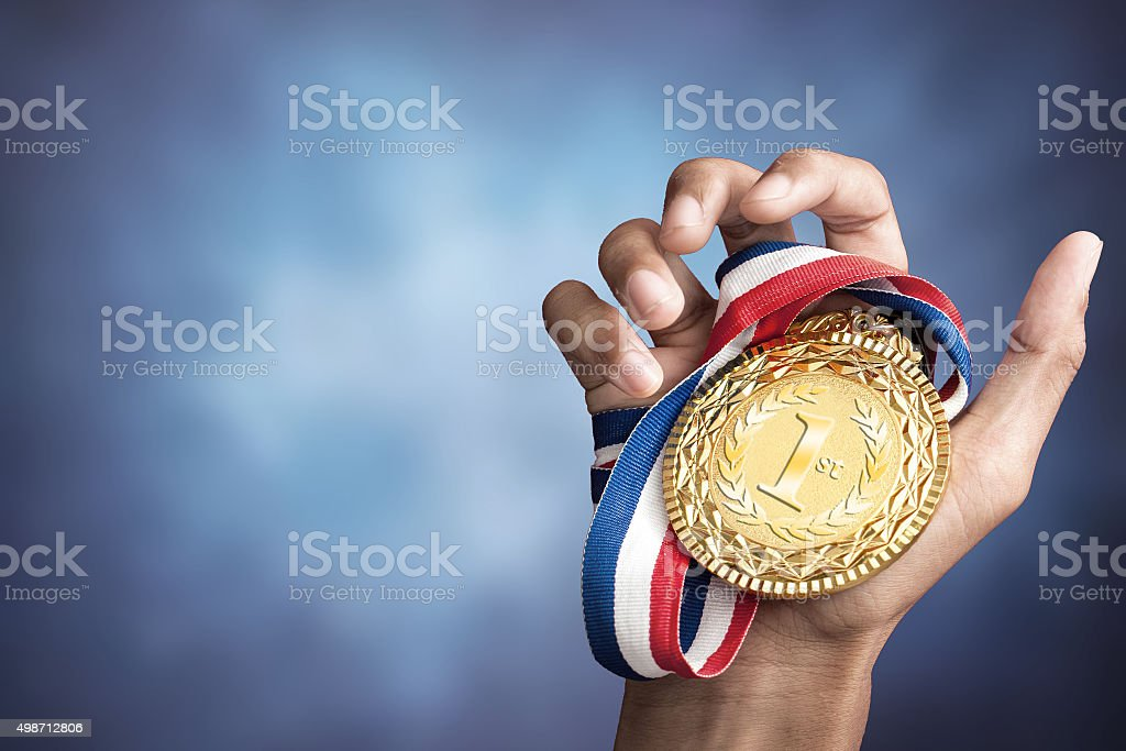hand holding up a gold medal stock photo