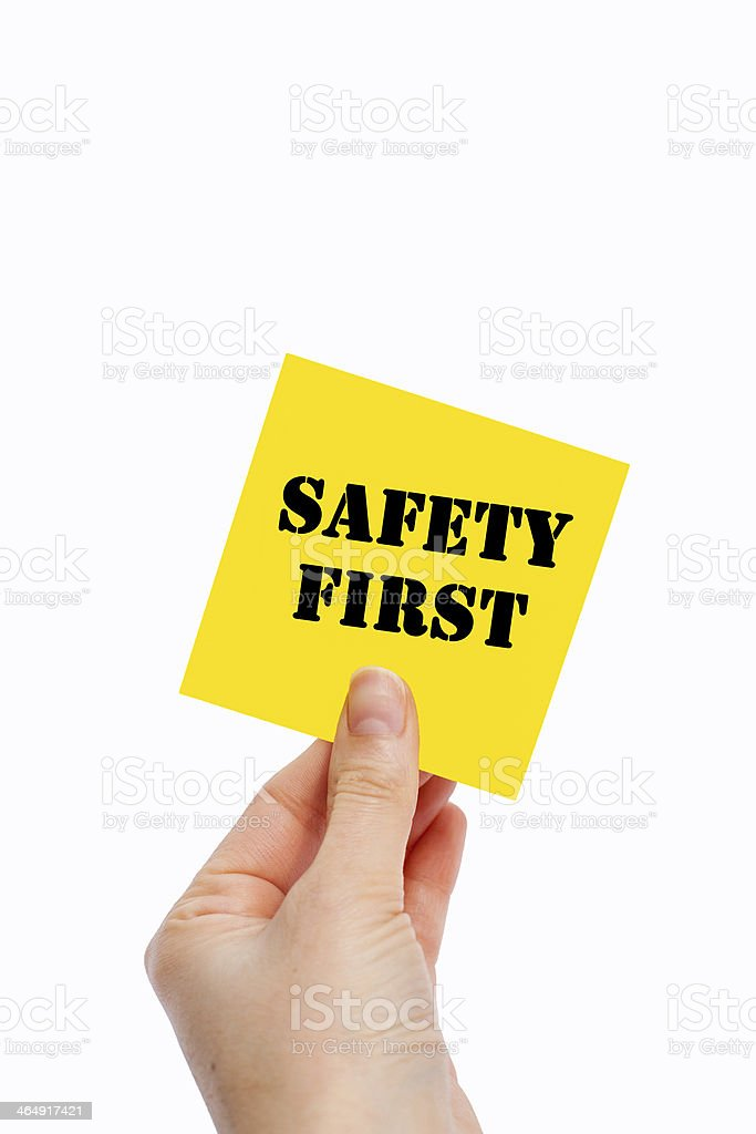 A hand holding up a yellow post-it reading Safety First stock photo