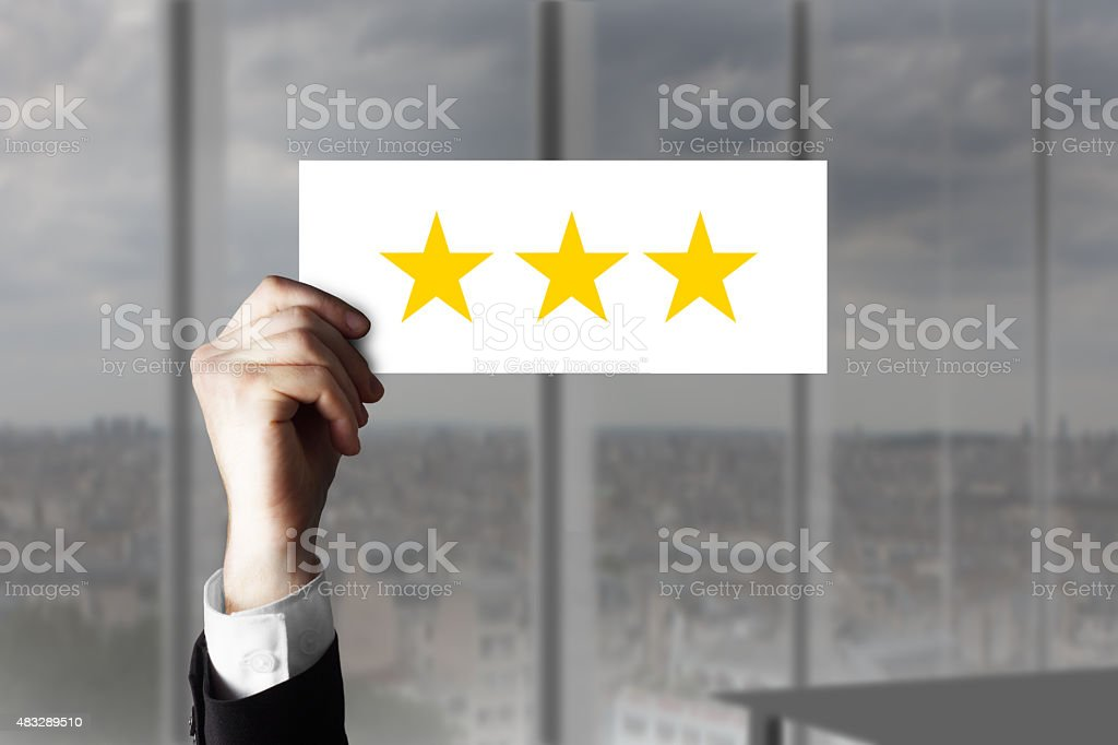 hand holding up small sign three rating stars stock photo