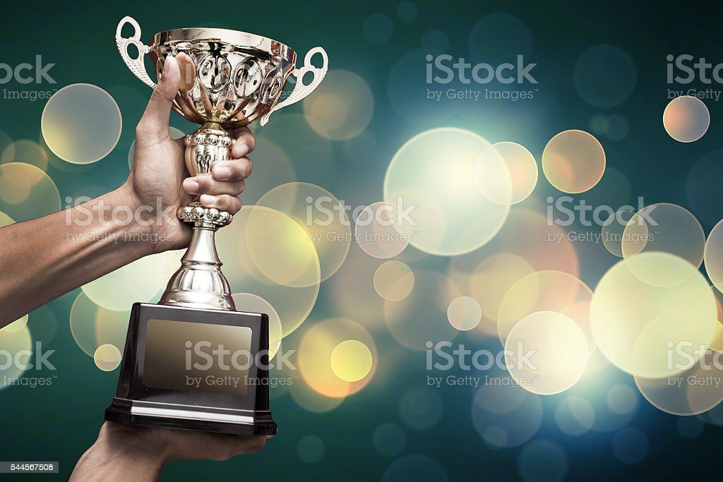 hand holding up trophy stock photo