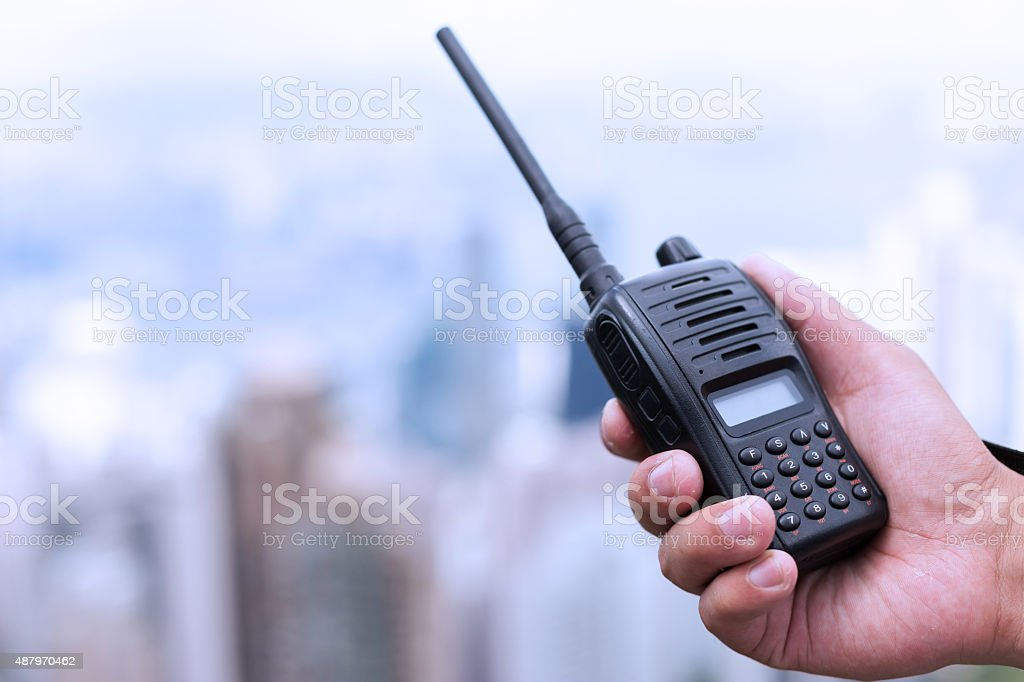 hand holding walky talky with cityscape as background stock photo