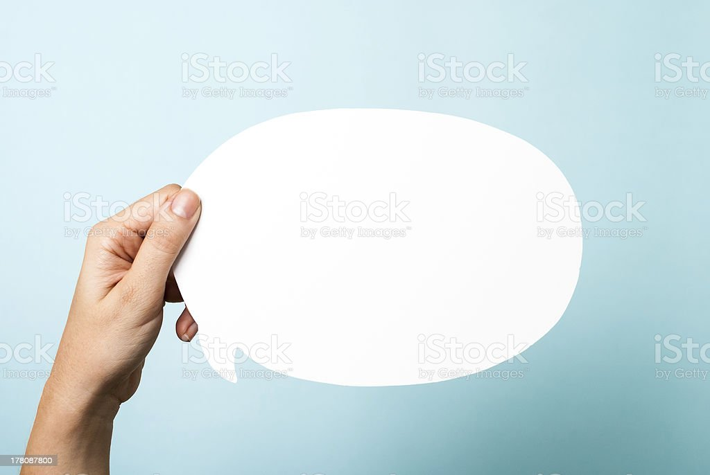 Hand holding white blank announce. Converse speech bubble, blue background stock photo