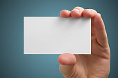 Hand holding white blank business visit card, gift, ticket, pass
