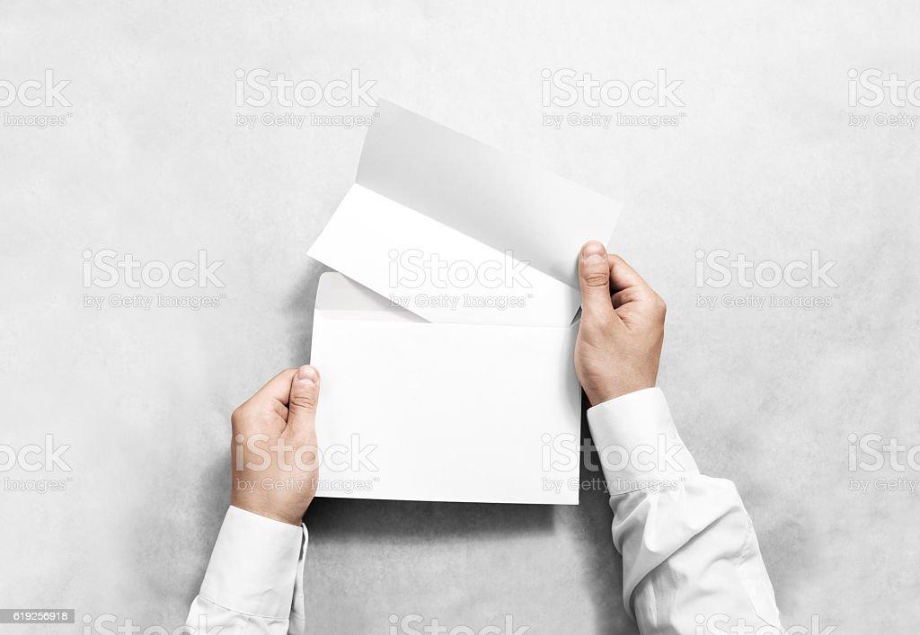 Hand holding white blank envelope and folded leaflet mockup, isolated stock photo