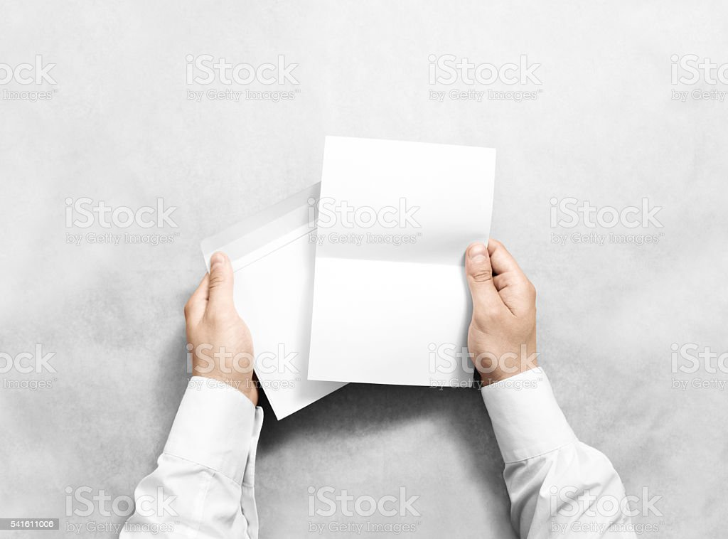 Hand holding white blank envelope and letter mockup, isolated. stock photo
