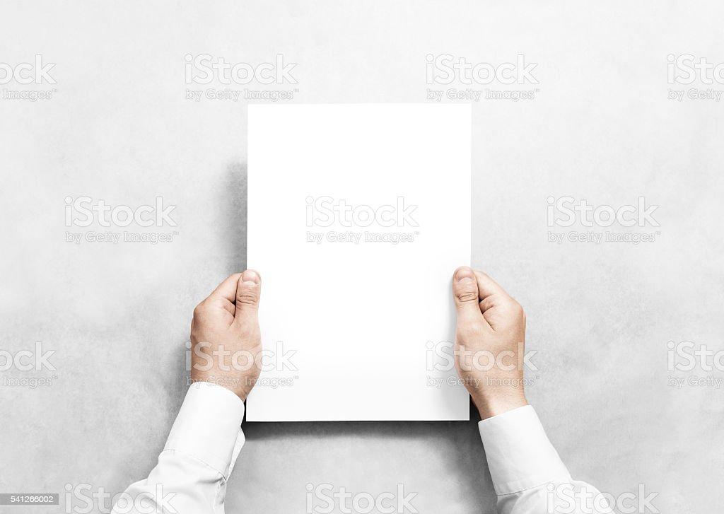 Hand holding white blank paper sheet mockup, isolated. stock photo