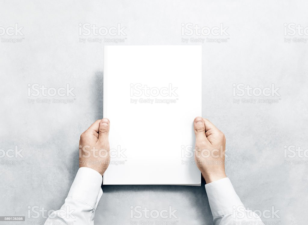 Hand holding white journal with blank cover mockup. stock photo