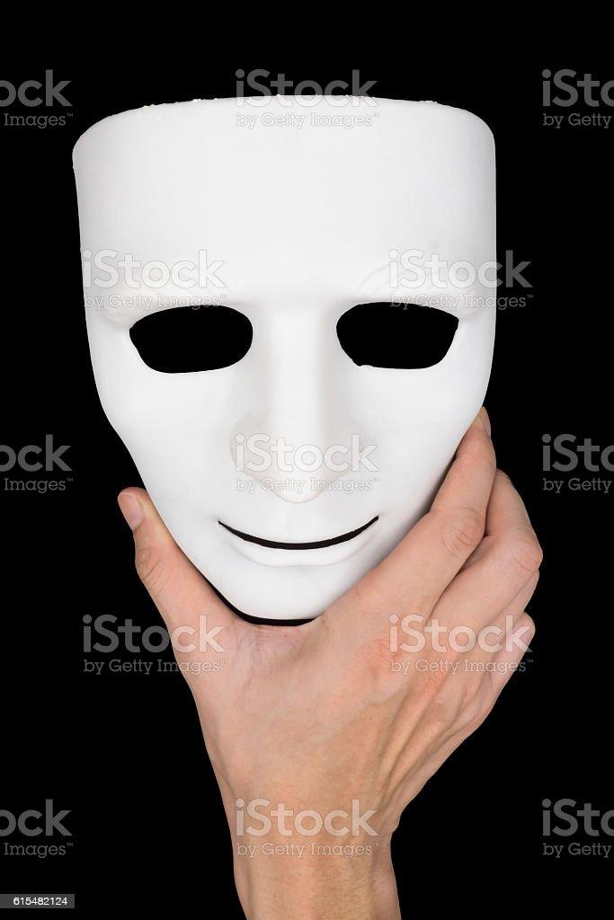 Hand holding white mask on black background. stock photo