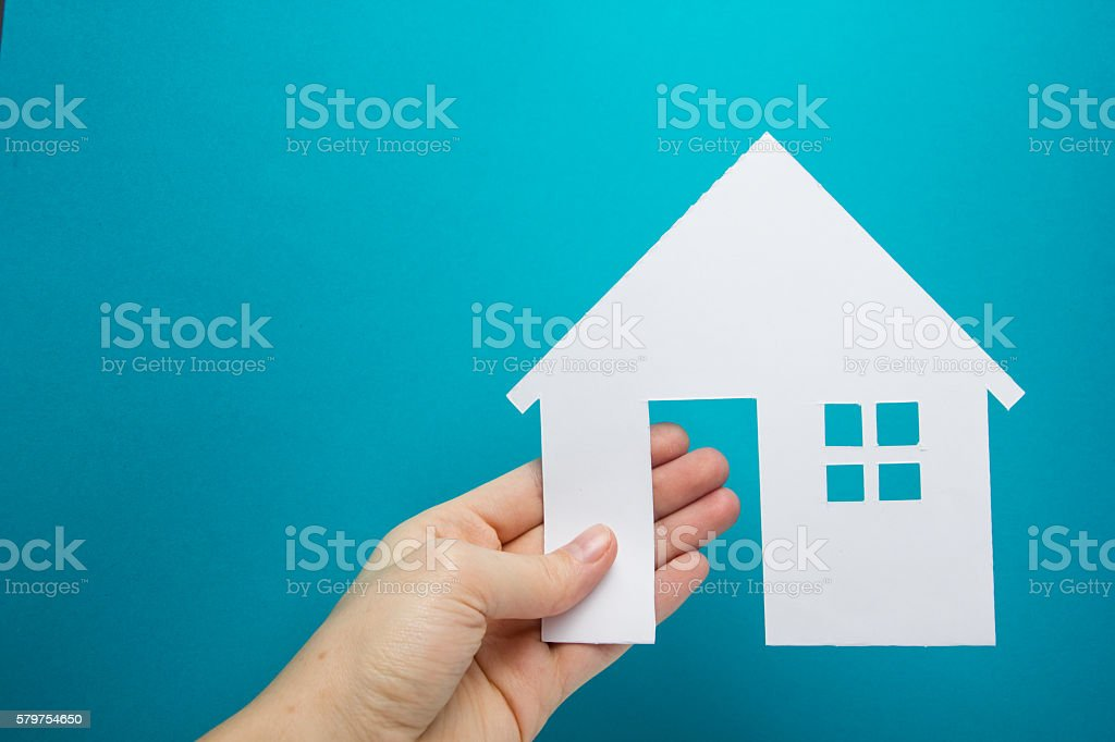 Hand holding white paper house figure on blue background. Real stock photo