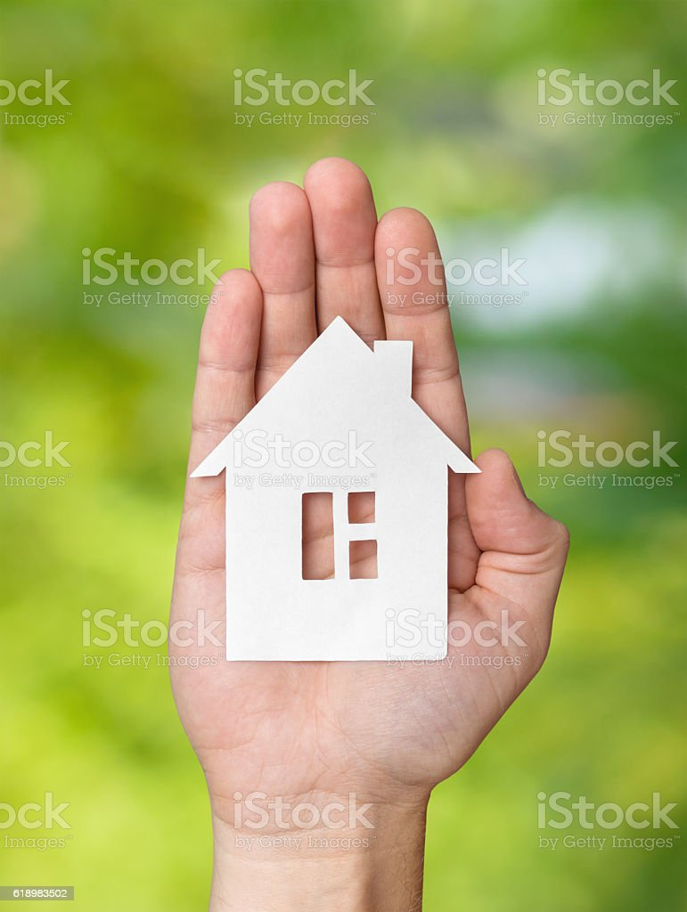Hand holding white paper house figure on green background stock photo
