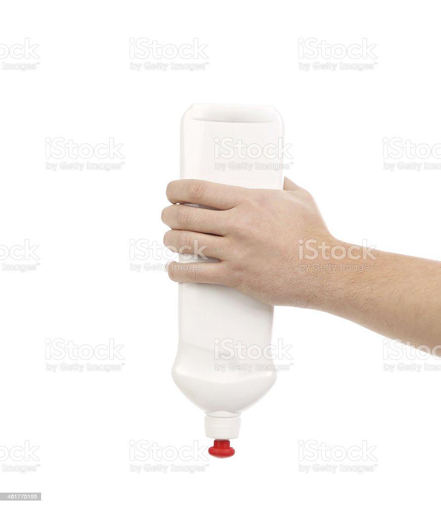 Hand holding white plastic bottle. stock photo