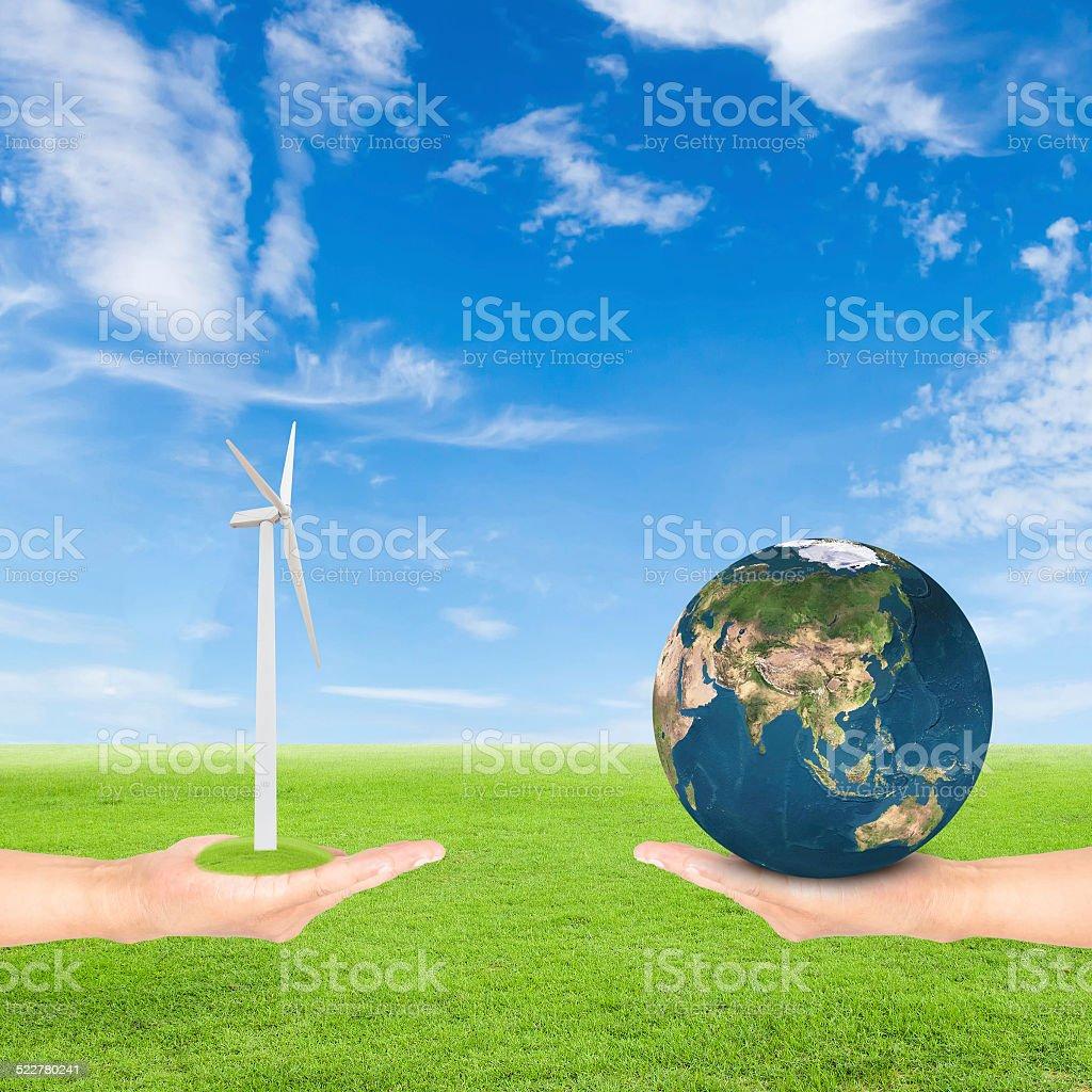 hand holding wind turbine and earth stock photo