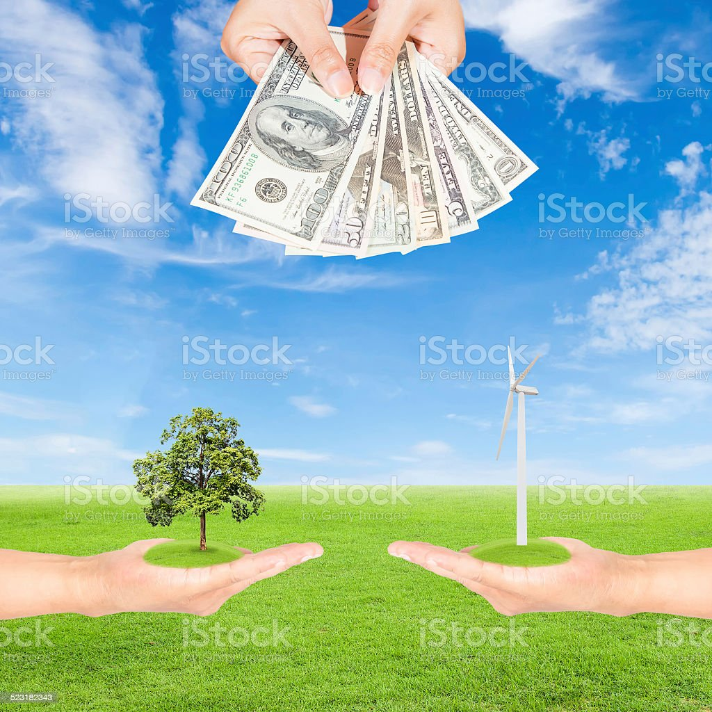hand holding wind turbine with tree and US Dollars banknote stock photo