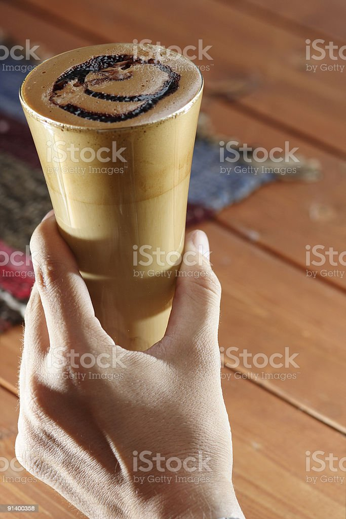 Hand holdnig a glass of ness coffee stock photo