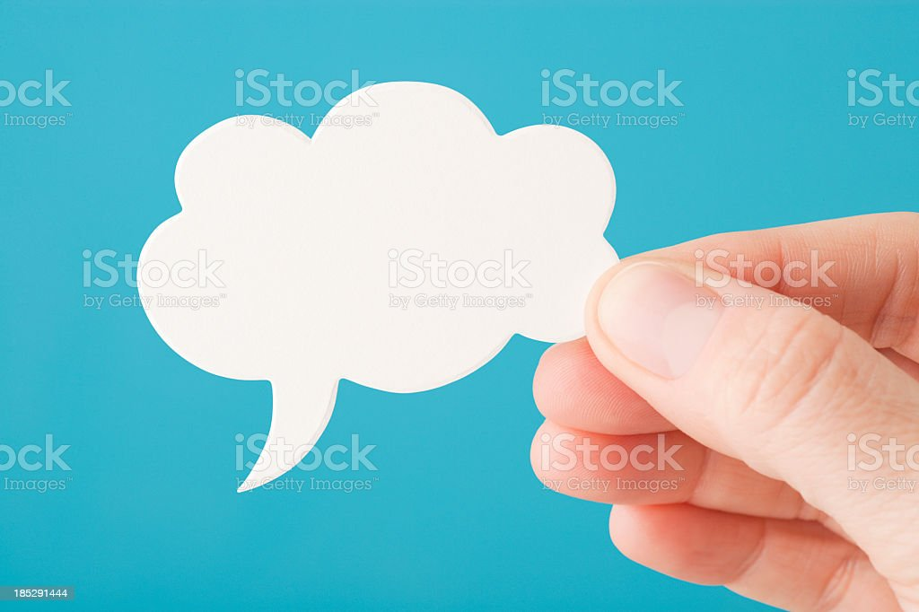 Hand holds a blank white speech bubble royalty-free stock photo