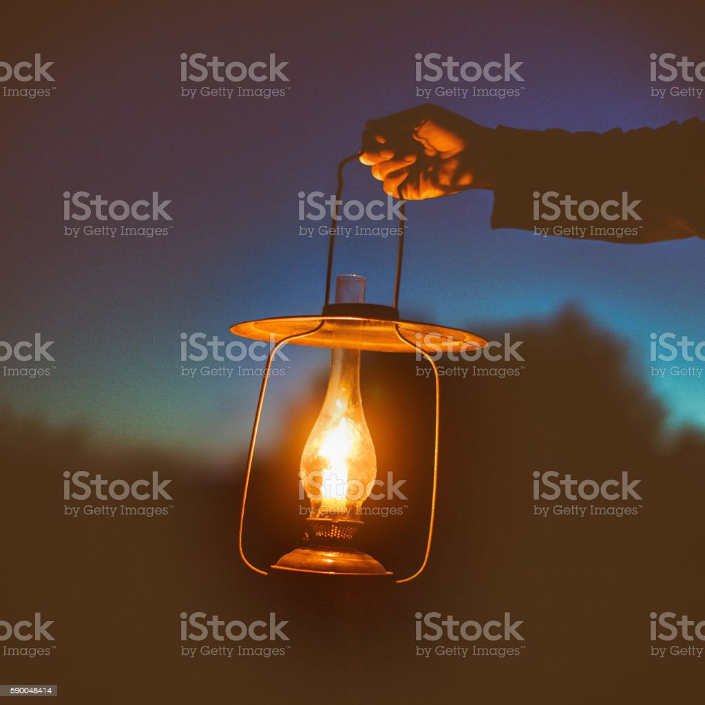 hand holds a large lamp outdoors in the dark stock photo