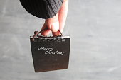 Hand holds a tag with the inscription Merry Christmas