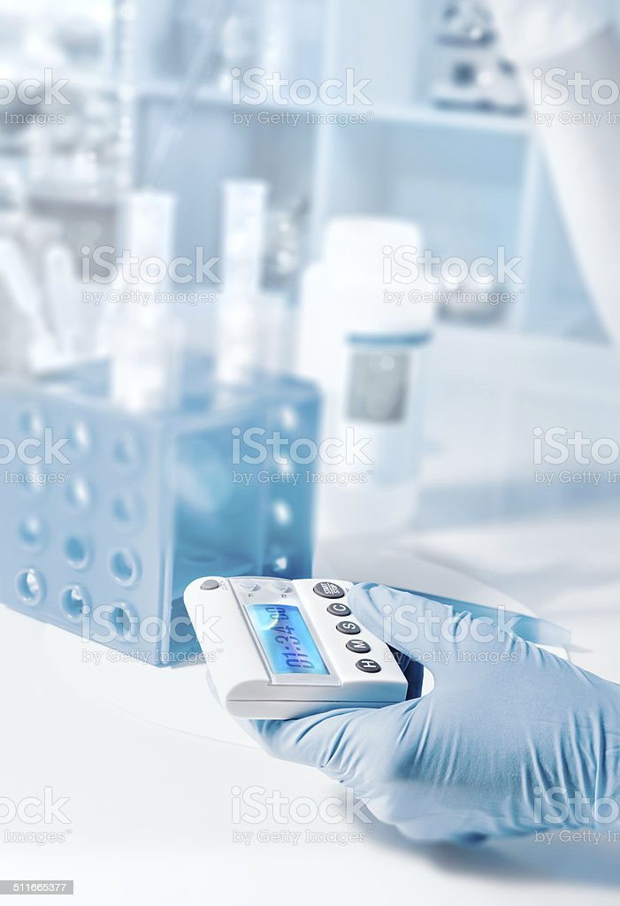 Hand holds a timer, scientific background stock photo