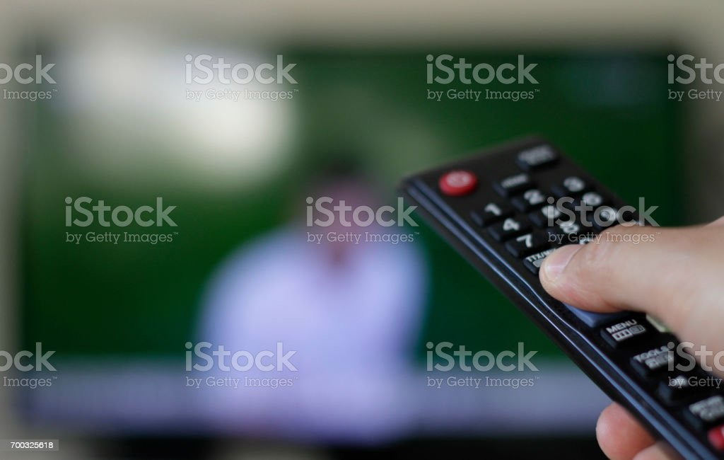 A hand holds a TV remote control stock photo