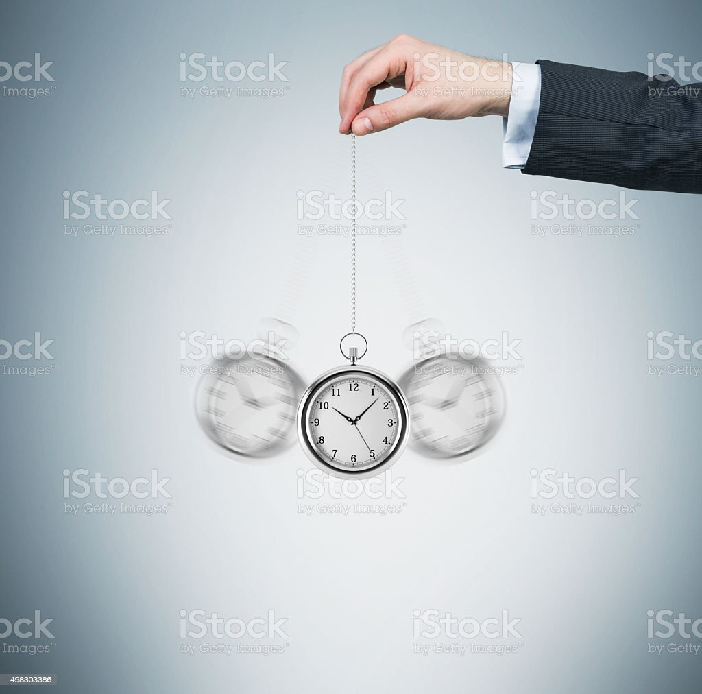 hand holds a watch in a chain as a pendulum stock photo