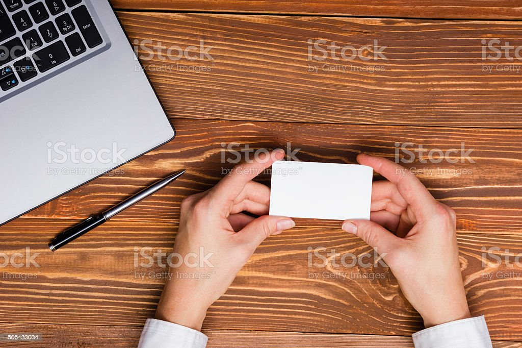 Hand holds a white business card on a white background stock photo