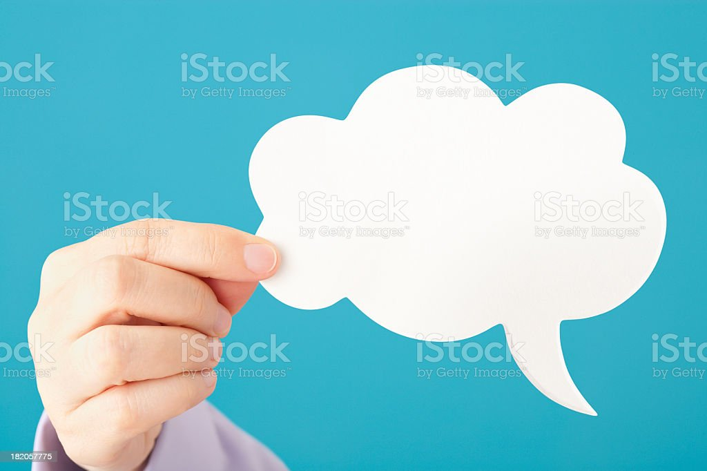 Hand holds blank cloud shaped speech bubble royalty-free stock photo