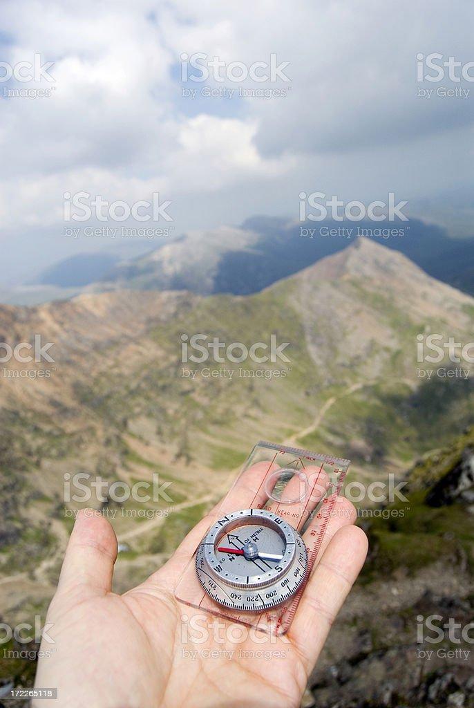 Hand holds compass towards vast landscape stock photo