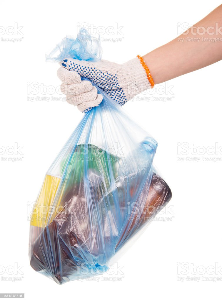 Hand holds garbage bag with household waste isolated on white stock photo