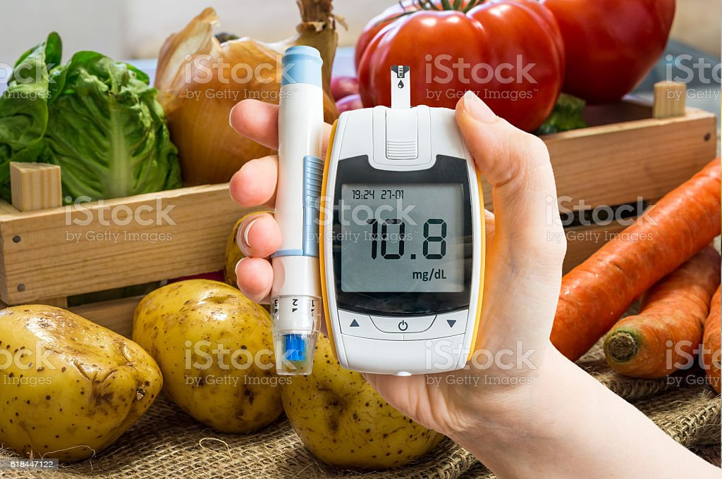 Hand holds glucometer for measuring glucose level. stock photo