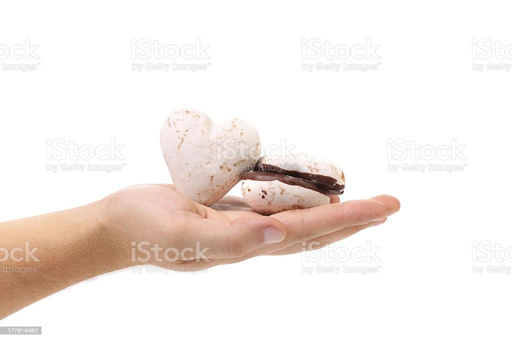 Hand holds heart shape chocolate meringues. stock photo