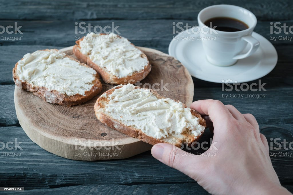 Hand holds homemade sandwiche with cream-cheese over a black wooden table. Wooden stand with sandwiches. Breakfast with coffee. stock photo