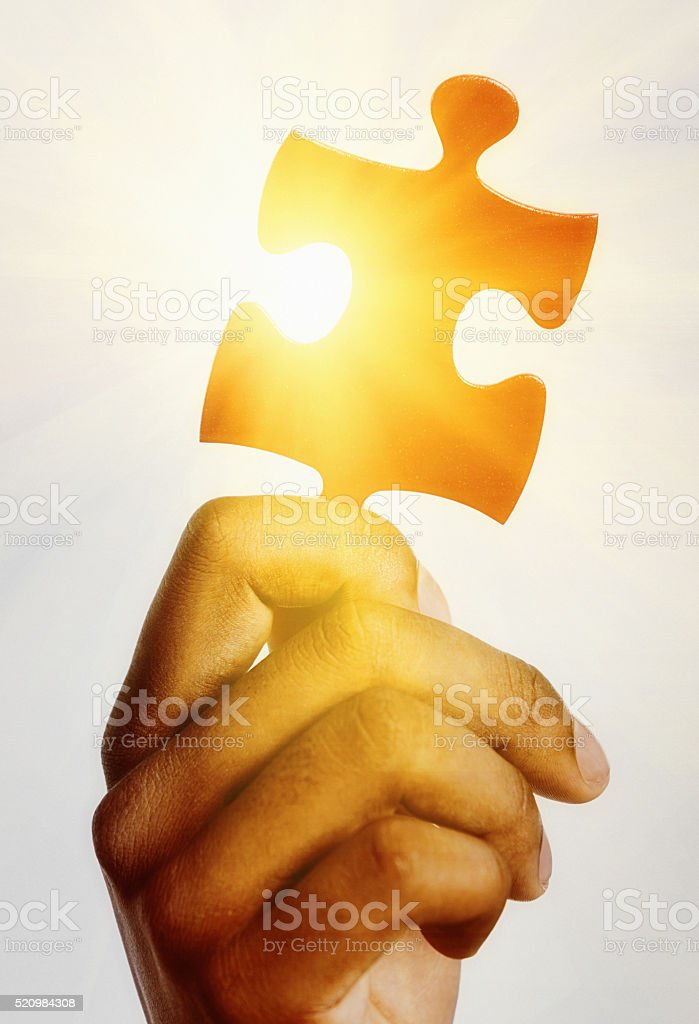 Hand holds jigsaw piece up against dazzling sun stock photo