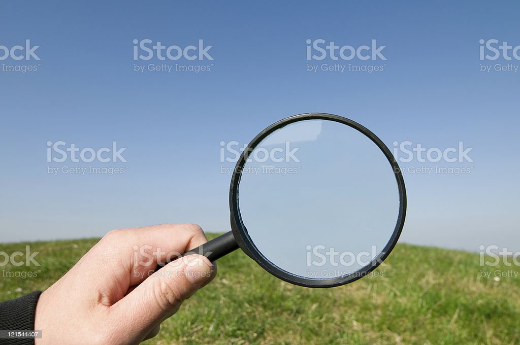 Hand holds magnifying glass up op a hill and sky royalty-free stock photo