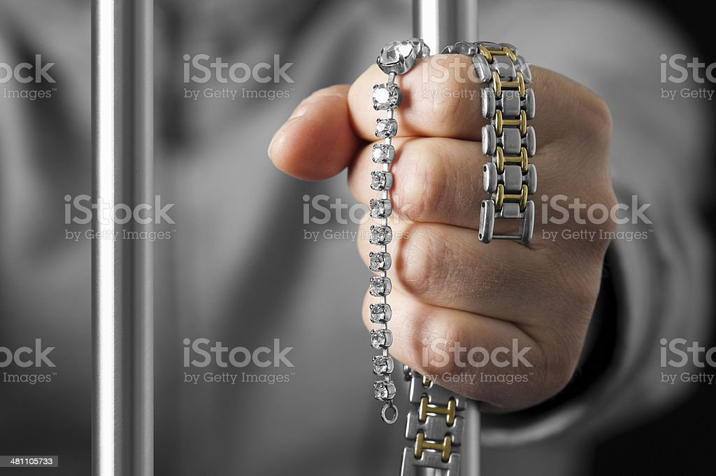 Hand holds prison bar and stollen jewellery royalty-free stock photo