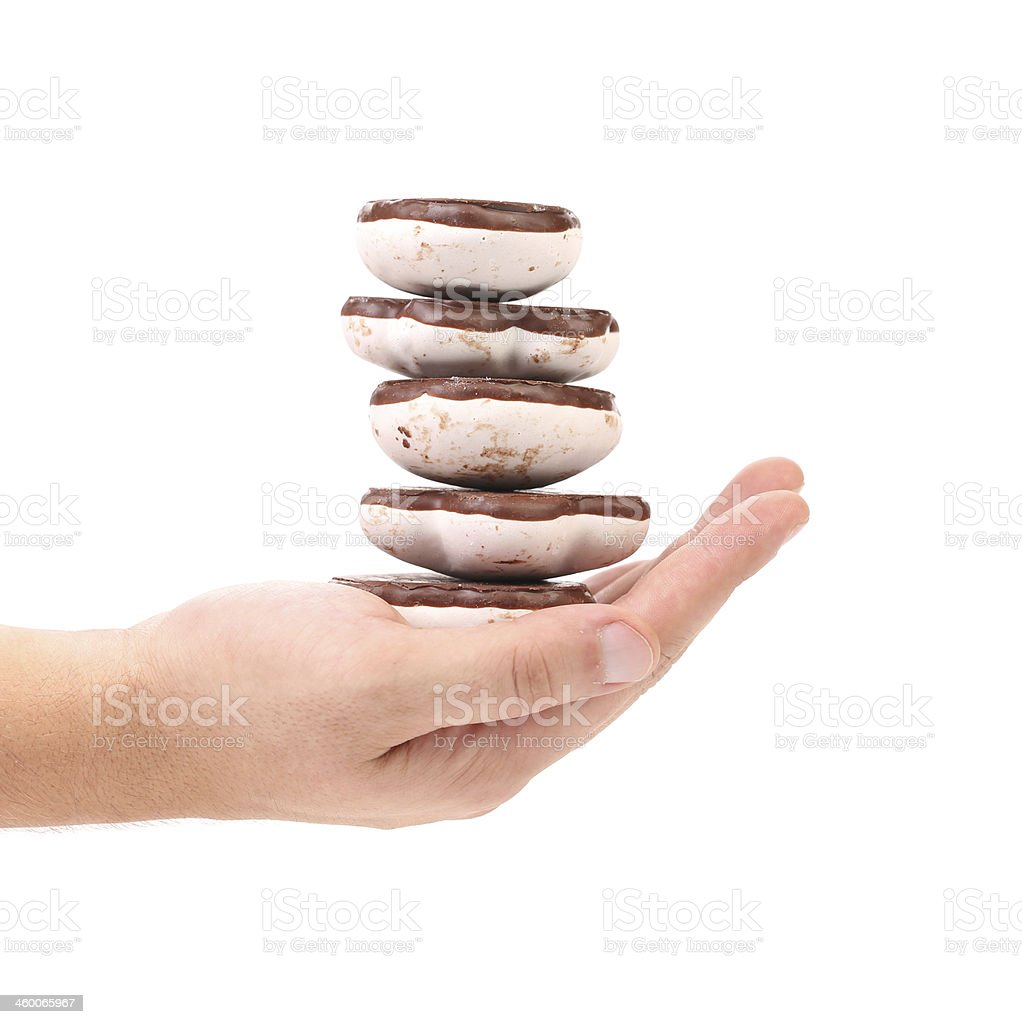 Hand holds stack of chocolate meringues. royalty-free stock photo