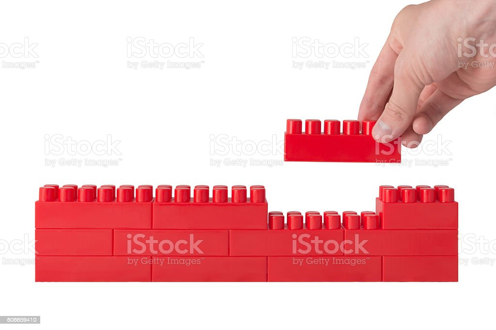 hand holds the last constructor block and completes the wall stock photo