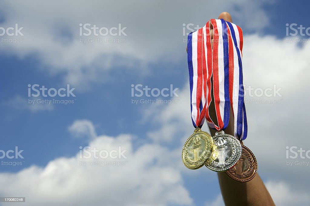 Hand Holds Up Gold Silver Bronze Medals in Sky stock photo