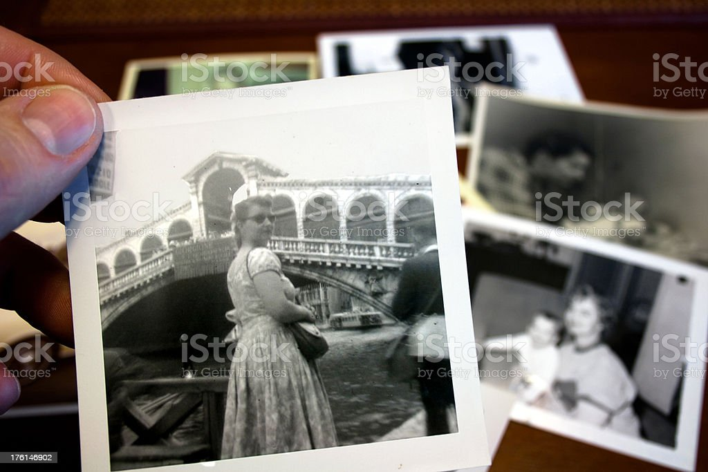 Hand holds Vintage photograph of 1950s woman sightseeing royalty-free stock photo