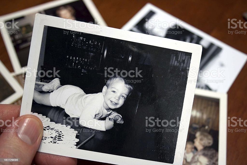 Hand holds Vintage photograph of child on table royalty-free stock photo