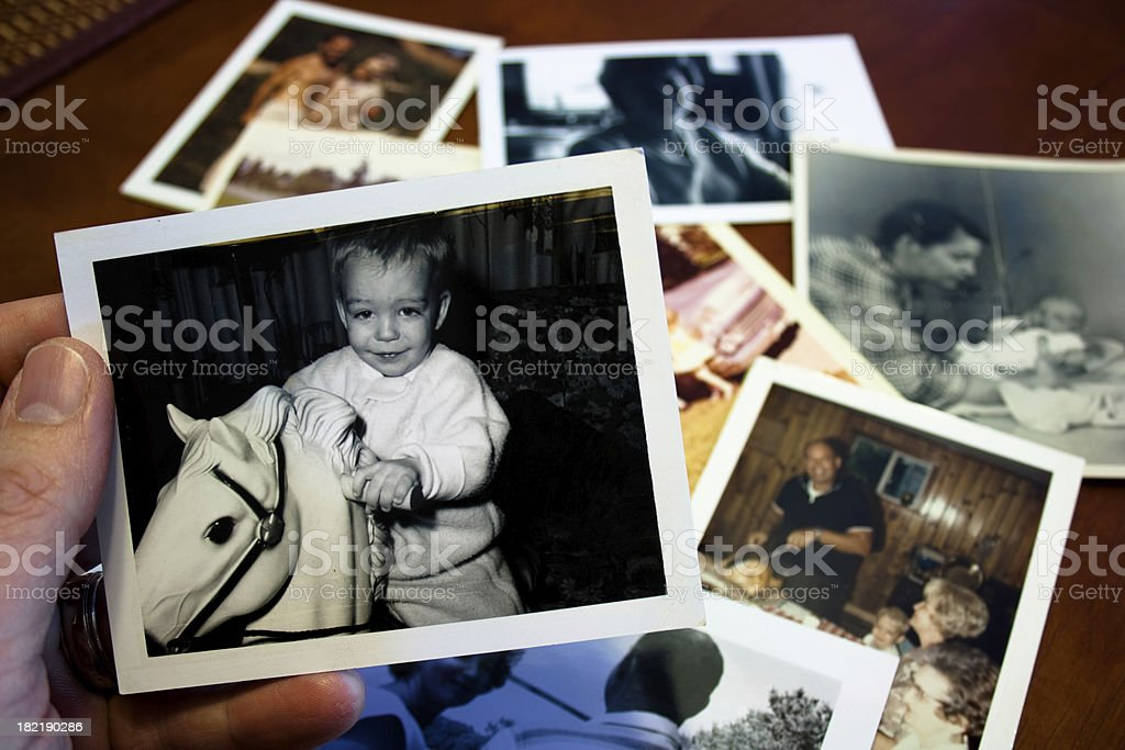 Hand holds Vintage photograph of child with hobby horse toy stock photo