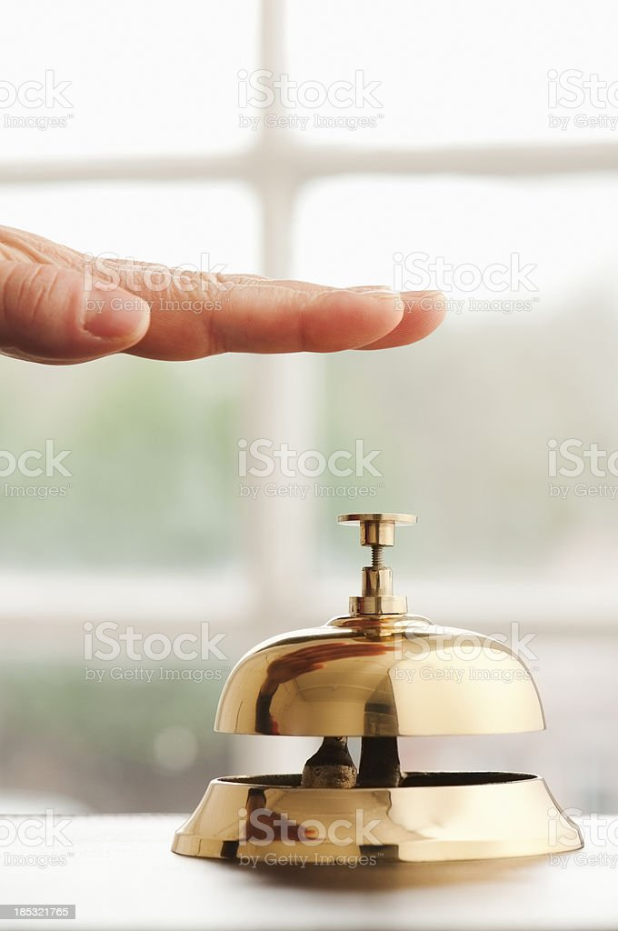 Hand hovering over service bell on desk beside window stock photo