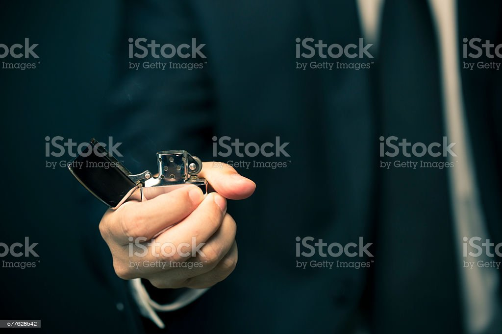 Hand igniting fire lighters on a black background stock photo